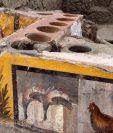 Detalle de la decoración descubierta en un termopolio, en el área arqueológica de Pompeya. (Foto Prensa Libre: EFE)