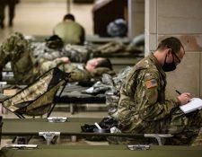 Soldados de la Guardia Nacional estadounidense toman un descanso en el centro de visitantes del Capitolio, en Washington. (Foto Prensa Libre: AFP)