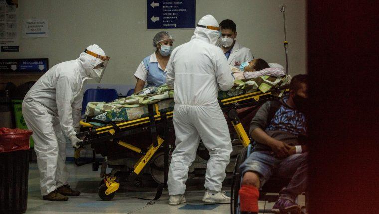 Paramédicos con equipo de protección para evitar el contagio de coronavirus ingresan a una mujer al área de emergencias del Hospital San Juan de Dios. (Foto Prensa Libre: EFE)