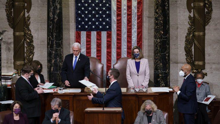 El Vicepresidente de Estados Unidos,  Mike Pence, y Nancy Pelosi luego de leer la certificacion final del Colegio Electoral que da la victoria a Joe Biden. (Foto Prensa Libre: EFE)