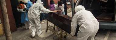 AME8839. CIUDAD DE GUATEMALA (GUATEMALA), 11/01/2021.- Fotografía de archivo fechada el 29 de junio de 2020, que muestra a paramédicos mientras retiran el cuerpo de un hombre fallecido por coronavirus, en Ciudad de Guatemala (Guatemala). Guatemala se convirtió este domingo en el primer país de Centroamérica en llegar a los 5.000 fallecidos por la covid-19, aunque según expertos la cifra es mucho mayor debido al subregistro de decesos. EFE/ Esteban Biba