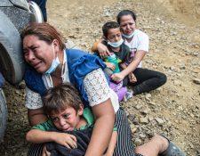 Una migrante llora junto a su hijo luego que la Policía disolviera la caravana de miles de personas que bloqueba  una carretera en Vado Hondo, Chiquimula. (Foto Prensa Libre: EFE)