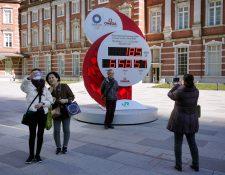 Las personas se toman fotos en un reloj que marca el conteo hacia los Juegos Olímpicos de Tokio 2022. Foto Prensa Libre: EFE.