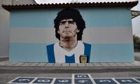 (FILES) This file photo taken on December 2, 2020 shows a graffiti depicting Argentine football legend Diego Maradona by street artist Stilos Ilias, painted on a wall off a primary school in Kalamaria neighborhood of Thessaloniki. - Diego Maradona's death on November 25, 2020 shook the world of sport. The surprise and pain over the death of the football troubled genius at the age of 60 reinforced his myth and multiplied the tributes that seek to immortalize him. (Photo by Sakis MITROLIDIS / AFP) / RESTRICTED TO EDITORIAL USE - MANDATORY MENTION OF THE ARTIST UPON PUBLICATION - TO ILLUSTRATE THE EVENT AS SPECIFIED IN THE CAPTION