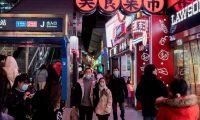 Pobladores usan mascarilla en una de las calles de Wuhan, China, a donde llegará un equipo de la OMS a investigar el origen del coronavirus. (Foto Prensa Libre: AFP)