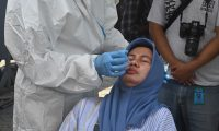 A health worker takes a swab from a journalist to test for the Covid-19 coronavirus before boarding a ship taking part in search and recovery operations for the Sriwijaya Air Boeing 737-500 passenger aircraft at Tanjung Priok port, north of Jakarta on January 11, 2021, following the January 9 crash of flight SJ182 into the Java Sea minutes after takeoff. (Photo by ADEK BERRY / AFP)