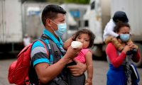 A Honduran migrant who voluntarely returns to Honduras feeds a toddler in El Florido, Chiquimula, Guatemala on January 19, 2021. - On buses and trucks, Guatemala transported Tuesday several groups of migrants who were part of a US-bound caravan back to Honduras, after police and military officers forced them to desist from the crossing. (Photo by Johan ORDONEZ / AFP)