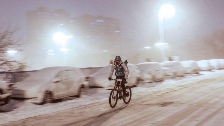 Un repartidor en bicicleta circula por la madrileña avenida Ramón y Cajal completamente nevada, en una jornada en la que la Agencia Estatal de Meteorología ha activado el nivel rojo por la previsión de fuertes nevadas. (Foto Prensa Libre: EFE)