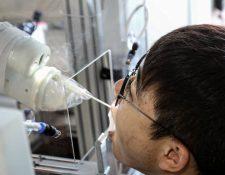 Una máquina robot toma una muestra de un hisopo de un hombre para realizar la prueba del coronavirus covid-19 en Shenyang. (Foto Prensa Libre: AFP)