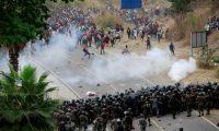 AME9885. CHIQUIMULA (GUATEMALA), 17/01/2021.- Soldados y policías guatemaltecos forman una barricada humana y lanzan gases lacrimógenos para detener a los migrantes hondureños que caminan por una carretera hoy, en Chiquimula (Guatemala). Las fuerzas de seguridad de Guatemala detuvieron y reprendieron violentamente este domingo a una caravana migrante compuesta por miles de hondureños, que pretenden llegar a México y posteriormente a Estados Unidos en busca del sueño americano. Según constató Efe, los migrantes fueron atacados a palos y con bombas lacrimógenas por miembros del Ejército de Guatemala cuando intentaron avanzar en una carretera al oeste del país, donde permanecen varados desde la noche del sábado. EFE/ Esteban Biba