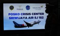 A security personnel stands in front of a sign for a crisis centre for Sriwijaya Air flight SJY182 at the Soekarno-Hatta international airport in Tangerang near Jakarta on January 9, 2021, after contact with the Boeing 737 aircraft was lost and feared to have crashed into the sea shortly after take-off. - An Indonesian budget airline with 62 people on board is suspected to have crashed into the sea shortly after the Boeing 737 took off from Jakarta airport on January 9, authorities said. (Photo by FAJRIN RAHARJO / AFP)