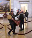 Un hombre fue captado cuando se llevaba un atril del capitolio durante la jornada de protestas de simpatizantes del presidente Donald Trump. (Foto Prensa Libre: AFP)
