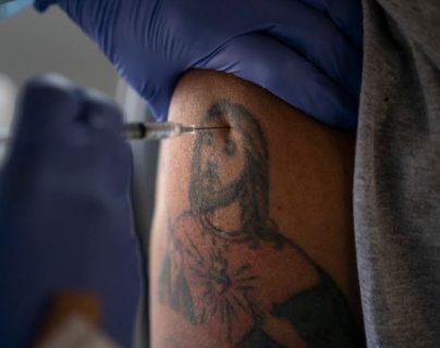 EL trabajador agrícola Jorge Americano recibe la vacuna de Pfizer en su brazo tatuado en Mecca, California. (Foto Prensa Libre: VAO)