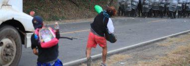 Migrantes lanzan piedras y botellas al contingente de la Policía que los desaloja en km 177 de Vado Hondo, Chiquimula, (Foto Prensa Libre: Carlos Hernández)