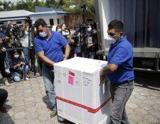 Dos hombres bajan de un camión una caja que contiene dosis de las vacunas contra la covid-19, en el Centro Nacional de Biológicos en Soyapango, El Salvador.  (Foto Prensa Libre: EFE)