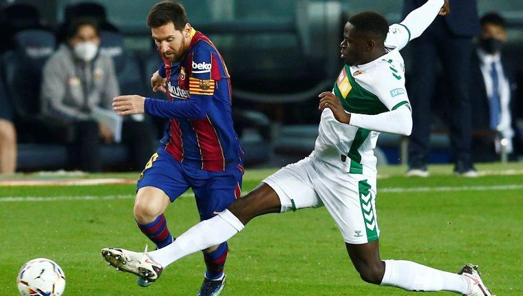 El delantero argentino del Barcelona Lionel Messi pelea un balón con el centrocampista del Elche Omenuke Mfulu durante el partido de La Liga que se disputa este miércoles en el Nou Camp. Foto Prensa Libre: EFE.