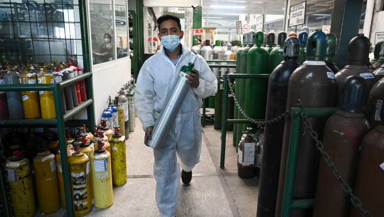 Un trabajador de Salud prepara tanques de oxígeno para ser distribuidos en hospitales  para personas infectadas con coronavirus. (Foto Prensa Libre: AFP)