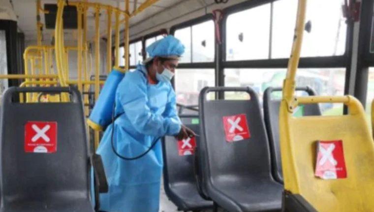 Un trabajador desinfecta una unidad de transporte público en Guatemala. (Foto Prensa Libre: Hemeroteca PL)