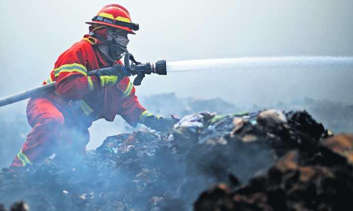 Sin importar el riesgo, un bombero lanza agua a las llamas, en uno de los pisos más bajos del vertedero de Amsa.  (Foto Prensa Libre: Carlos Hernández Ovalle)