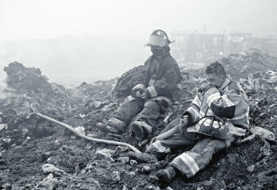 Mavel Monzón, de  21 años, del Cuerpo de Bomberos Municipales Departamentales,  y Óscar Franco, de 45 años, del Cuerpo Voluntario de Bomberos, trabajaron 18 días consecutivos para sofocar el incendio en el basurero de Amsa.  (Foto Prensa Libre: Carlos Hernández Ovalle)
