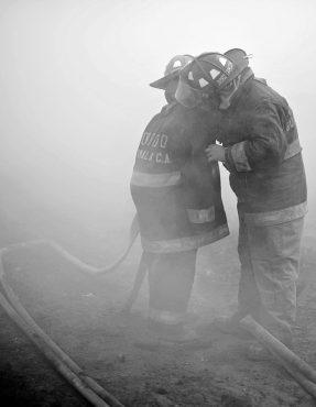 La galonista Sharon Ramos auxilia a uno de sus compañeros, en el momento en que una nube de humo no le permitía respirar.   (Foto Prensa Libre: Carlos Hernández Ovalle)