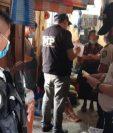 Agentes fiscales y de la Policía durante la captura de la mujer que tenía encadenada a su hija en Joyabaj, Quiché. (Foto Prensa Libre: PNC)