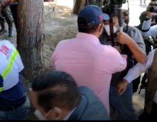 Momento en que un trabajador gubernamental empuja al periodista Héctor Cordero.