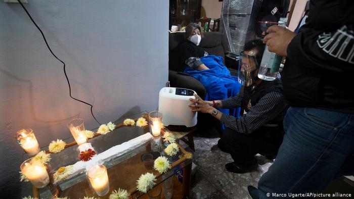Entrega de un concentrador de oxígeno a una mujer con COVID-19, frente al altar de su marido, quien murió a causa del virus en Iztapalapa, México.(Marco Ugarte/AP/picture alliance)