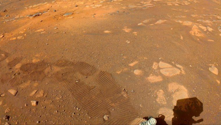 Las huellas del robot Perseverance pueden verse en esta imagen captada por una de sus cámaras el 5 de marzo. Uno de los objetivos de la misión es buscar señales de vida microbiana antigua. (NASA/JPL-CALTECH)