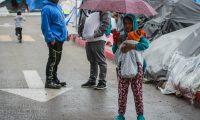 MEX6776. TIJUANA (MÉXICO), 12/03/2021.- Una niña migrante cubre a su hermano de la llovizna hoy en un campamento instalado en las inmediaciones del puerto fronterizo del Chaparral, ciudad fronteriza de Tijuana en el estado de Baja California Sur (México).El frío que ha hecho en las últimas semanas en Tijuana (norte de México) comienza a provocar enfermedades respiratorias en los niños de un campamento de migrantes que esperan tramitar su solicitud de asilo en Estados Unidos. EFE/Joebeth Terríquez