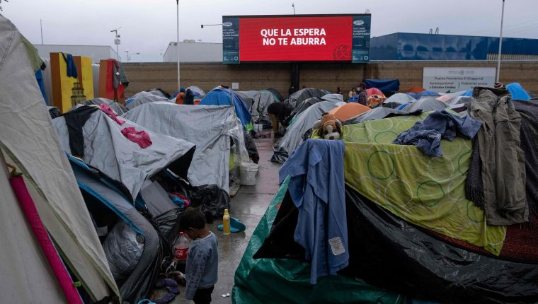 Un niño permanece fuera de unas carpas instaladas en Tijuana, frontera con EE. UU. donde los migrantes han empezado a acumularse debido a que intentan ingresar a EE. UU. (Foto Prensa Libre: AFP)