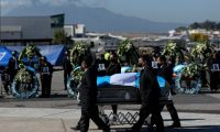 Relatives receive the coffins with the remains of Guatemalan migrants who were found murdered in the northern state of Tamaulipas last month, upon their arrival at the Air Force base, in Guatemala City on March 12, 2021. - On January 22, 19 charred bodies were found in Tamaulipas, a state on the border with the United States that has been rocked for years by organized crime gangs. Sixteen of the dead were determined to be Guatemalan and the other three of Mexican origin. (Photo by Johan ORDONEZ / AFP)
