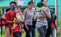 Migrants heading for the US are seen in Corinto, Honduras, on March 30, 2021 before trying to cross the border into Guatemala. - Guatemala on Monday authorized the use of force at its border with Honduras to block a new US-bound migrant caravan it said posed a coronavirus contagion risk. Hundreds of migrants gathered in northern Honduras started pushing into Guatemala on Tuesday, hoping to travel onwards to Mexico and the United States, according to Guatemalan migration authorities. (Photo by Wendell ESCOTO / AFP)