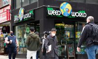 People walk past the Weed World store on March 31, 2021, in Midtown New York. - New York Governor Andrew Cuomo signed legislation legalizing recreational marijuana on March 31. 2021, with a large chunk of tax revenues from sales set to go to minority communities. New York joins 14 other US states and the District of Columbia in permitting cannabis after lawmakers in both state chambers, where Cuomo's Democratic Party holds strong majorities, backed the bill on March 30. (Photo by Kena Betancur / AFP)