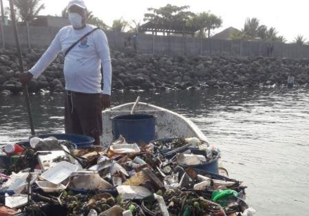 Trabajador transporta basura recolectada en la playa de Puerto San José. (Foto Prensa Libre: Tomada de página de la comuna)