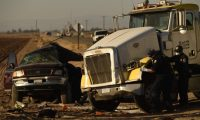 Investigators look over the scene of a crash between an SUV and a semi-truck full of gravel near Holtville, California on March 2, 2021. - At least 13 people were killed in southern California on Tuesday when a vehicle packed with passengers including minors collided with a large truck close to the Mexico border, officials said. (Photo by Patrick T. FALLON / AFP)