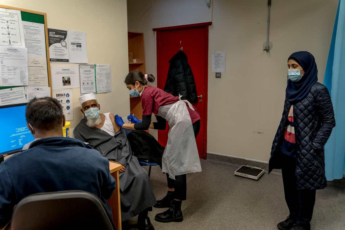 Una hija observa cómo su padre de 79 años se vacuna en Londres, el 28 de enero de 2021.(Andrew Testa/The New York Times)