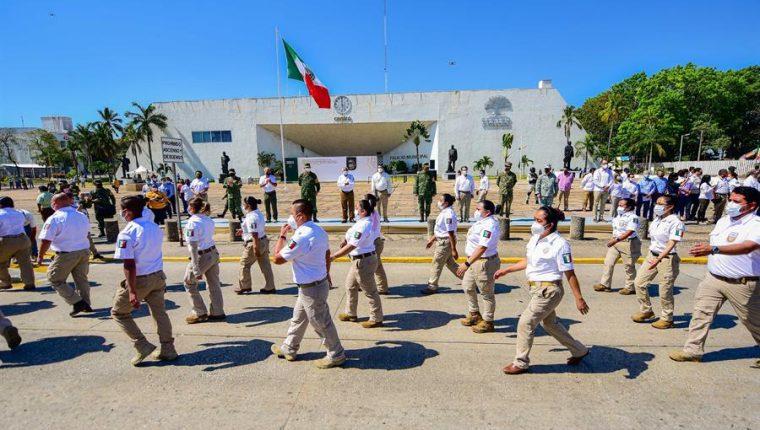 Integrantes del Instituto Nacional de Migración (INM) pasan frente a autoridades federales  en Villahermosa, estado de Tabasco, México. (Foto Prensa Libre: EFE)