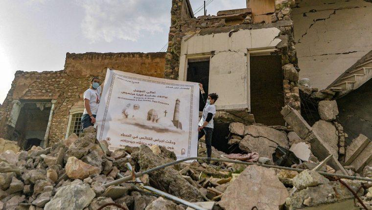 Los jóvenes despliegan un cartel que da la bienvenida al Papa Francisco sobre los escombros de una casa destruida junto a las ruinas de la Iglesia católica siríaca de la Inmaculada Concepción (al-Tahira) en la ciudad vieja de Mosul, en el norte de Irak. (Foto Prensa Libre: AFP)
