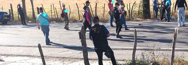 Policías, fiscales y hombres vestidos de civil con armamento pesado rodean la escena donde se observa, además, casquillos en el asfalto.