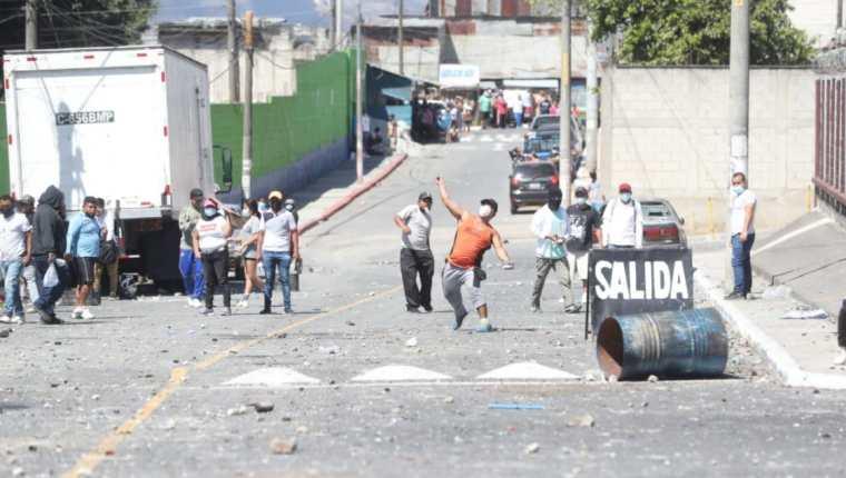 Supuestos invasores lanzan piedras contra vecinos de Nimajuyú. (Foto Prensa Libre: Erick Ávila)