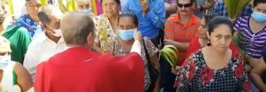 El sacerdote Rolando Peña le arrebata la mascarilla a una mujer  durante las actividades de Domingo de Ramos en Corquín, Copán, Honduras. (Foto Prensa Libre: Captura de video)