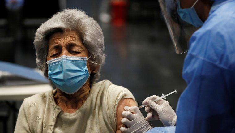 La vacunación en la segunda fase incluye a adultos mayores de 70 años. En la foto una anciana recibe la vacuna en Colombia. (Foto Prensa Libre: EFE)