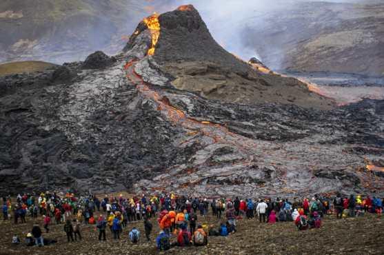 Los excursionistas observan la lava que fluye del volcán Fagradalsfjall en erupción a unos 40 km al oeste de la capital islandesa, Reykjavik. (Foto Prensa Libre: AFP)
