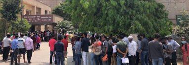 Gente esperando una prueba de covid frente a un hospital administrado por el gobierno en Noida.