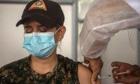 AME8363. CIUDAD DE GUATEMALA (GUATEMALA), 08/04/2021.- Fotografía que muestra a un integrante del servicio de salud mientras vacuna contra la covid-19 a una integrante de brigadas departamentales al Servicio de Sanidad Militar y al Batallón Humanitario y de Rescate el 7 de abril de 2021 en Ciudad de Guatemala (Guatemala). La vacunación contra la covid-19 en Guatemala camina a paso lento con los peores índices del continente al respecto y también con muchas dudas de expertos sobre la transparencia del proceso. EFE/Esteban Biba