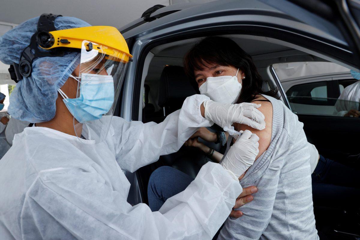 Una mujer recibe una dosis de vacuna contra el covid-19, dentro de su vehículo, en Bogotá, Colombia. (Foto Prensa Libre: EFE)