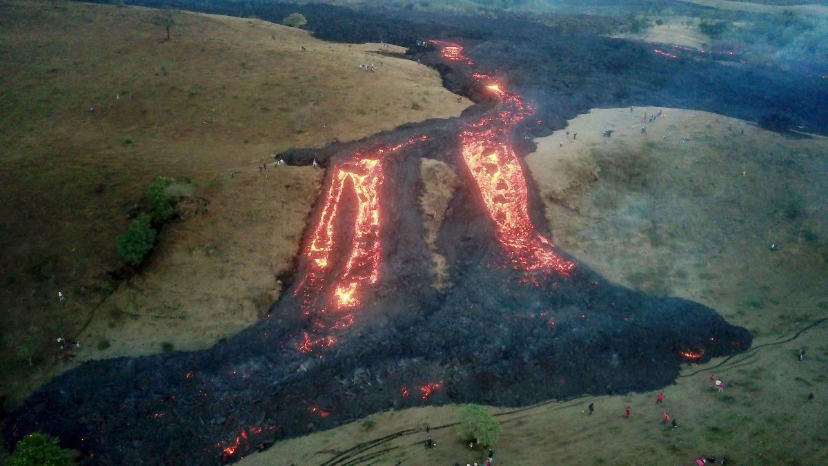 Vista aérea hoy desde un dron que muestra personas alrededor de uno de los ríos de lava causados por el volcán de Pacaya, el 13 de abril de 2021 desde la aldea El Patrocinio de San Vicente Pacaya. (Foto Prensa Libre: EFE)