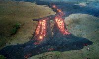 AME9841. SAN VICENTE PACAYA (GUATEMALA), 14/04/2021.- Vista aérea desde un dron que muestra personas alrededor de uno de los ríos de lava causados por el volcán de Pacaya, el 13 de abril de 2021 desde la aldea El Patrocinio de San Vicente Pacaya (Guatemala). Las corrientes de lava continúan su rumbo con dirección a las comunidades El Rodeo y El Patrocinio, enclavadas en las faldas del volcán, que ya suma más de dos meses de intensa actividad. Algunas de las casas de los pobladores están a menos de un kilómetro de distancia y el avance de los ríos de lava, lento pero constante, mantiene en vilo a la población. EFE/Esteban Biba
