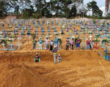 TOPSHOT - Aerial picture showing a burial taking place at an area where new graves have been dug up at the Nossa Senhora Aparecida cemetery in Manaus, in the Amazon forest in Brazil, on April 22, 2020. - The new grave area hosts suspected and confirmed victims of the COVID-19 coronavirus pandemic. More than 180,000 people in the world have died from the novel coronavirus since it emerged in China last December, according to an AFP tally based on official sources. (Photo by Michael DANTAS / AFP)